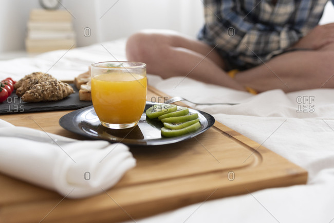 Close up of women's legs and a breakfast tray with fruits on a bed.