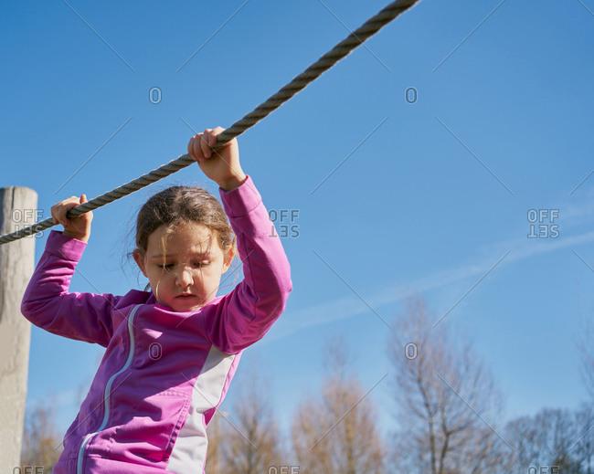 Girl on children's zip line looks down