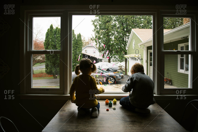 Two children painting on the window together