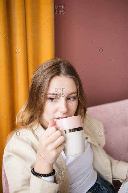 Young woman close-up drinks tea, coffee in ceramic cup in living room