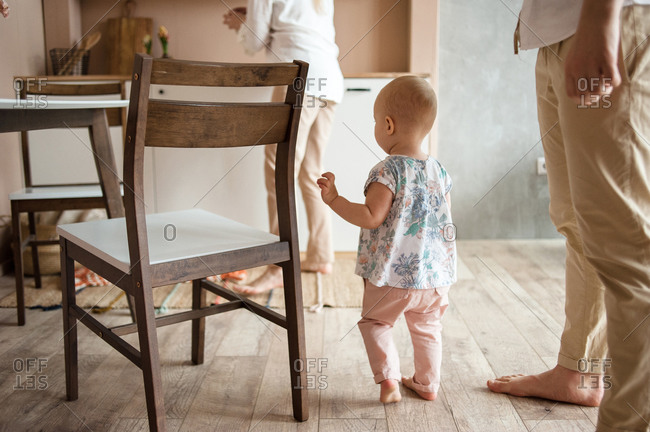 Little baby walks on wooden floors in the kitchen