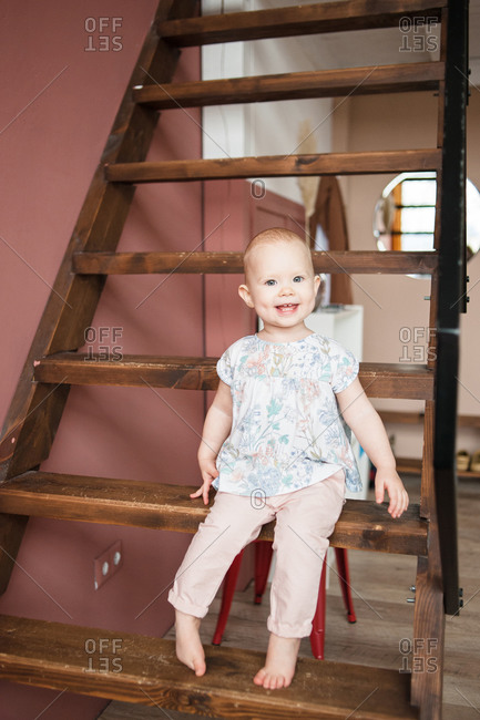 Cute smiling baby girl sits on wooden stair in modern apartment.