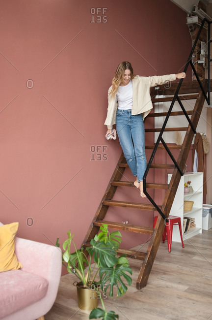 Young woman playfully descends wooden stairs at home holding railing.