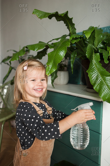 Smiling child with water sprayer in hands watering plants at home