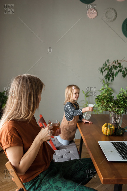 Mother with tea cup rests and looks at child who watering green plants