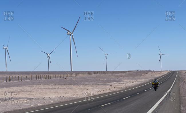 Man riding his ADV motorbike at wind farm in the remote Atacama desert