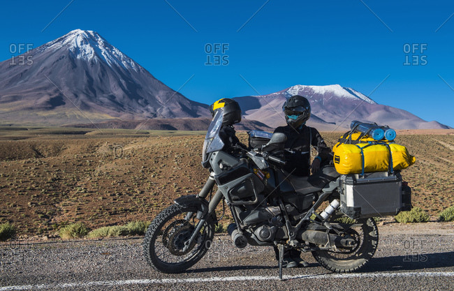 Woman behind ADV motorbike, in front of the stratovolcano Licancabur