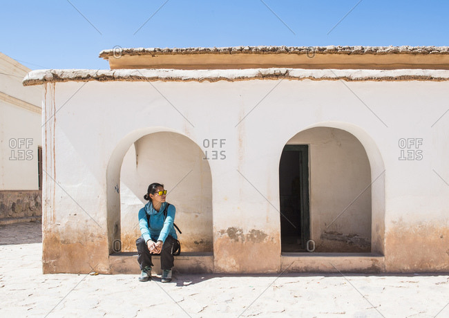 Woman waiting in archway at small village in Purmamarca, Argentina