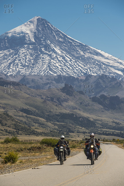 Neuquen, Neuquen, Argentina - March 16, 2017: Couple on touring motorbikes. Lanin volcano in the back, Argentina