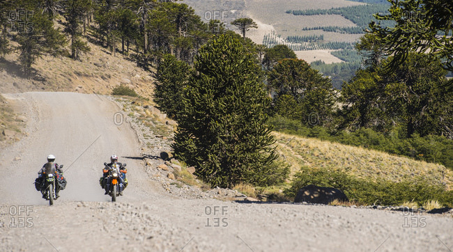 Couple on touring motorbikes driving on gravel road in Argentina