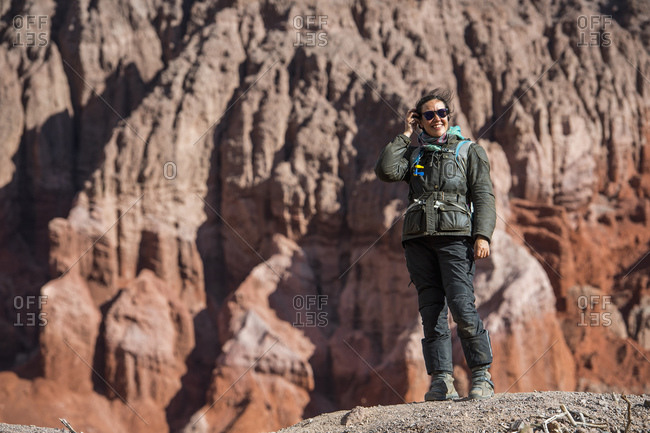 Woman in motorcycle gear, standing in front of red sandstone formation