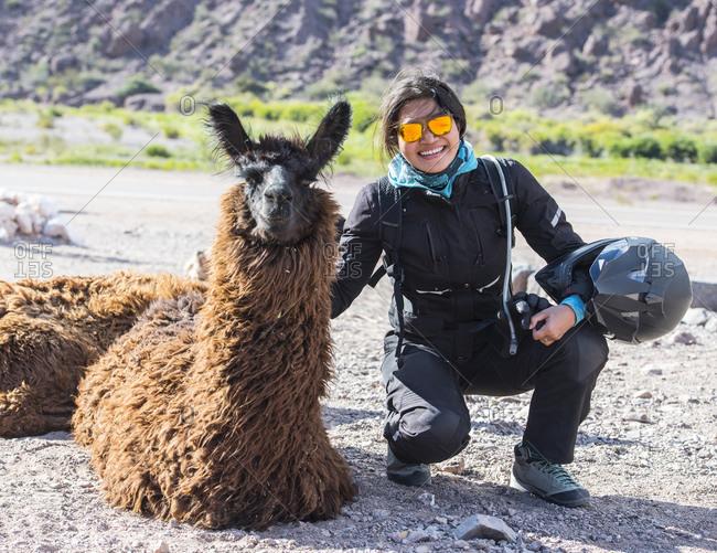 Woman in motorcycle gear crouching next to llama, Salta