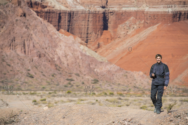 Man in motorcycle gear, standing in front of red sandstone formations