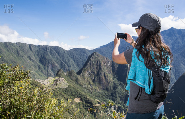 Woman takes a picture on smartphone of Machu Picchu on the Inca Trail