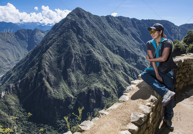 Woman resting on drywall on the Inca Trail close to Machu Picchu