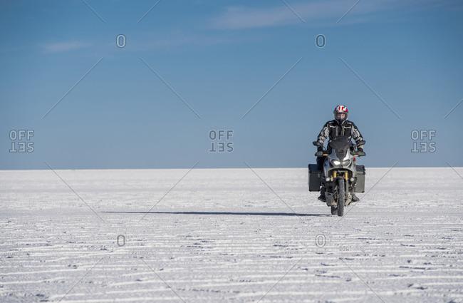 Man riding his touring motorbike on the salt flats of Uyuni in Bolivia