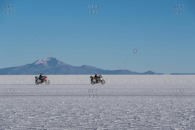 Two men riding touring motorbikes on the salt flats of Uyuni
