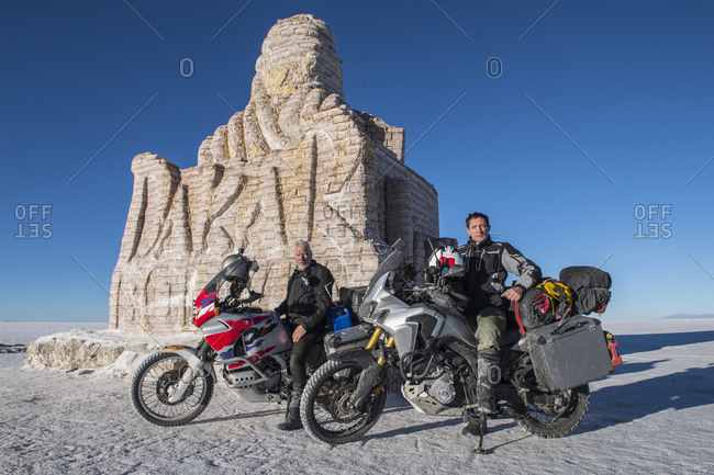 Two men and their touring motorbikes on the salt flats of Uyuni