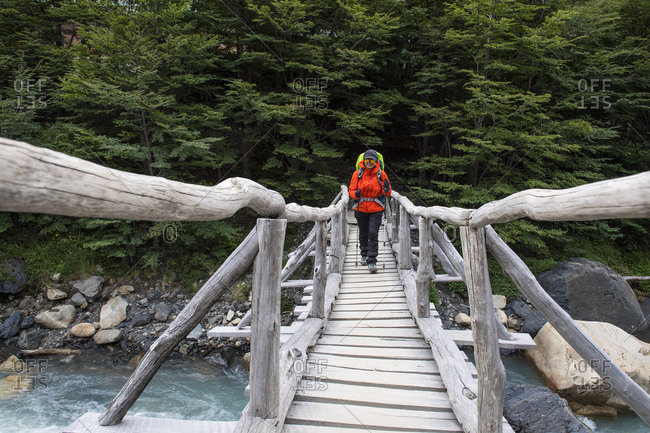Female hiker crossing wooden bridge on the way up to Torres del Paine
