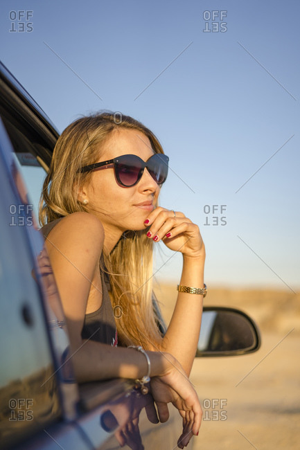 Young blond caucasian woman in a car in the desert