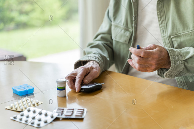 Midsection of retired diabetic senior man examining himself while sitting at table