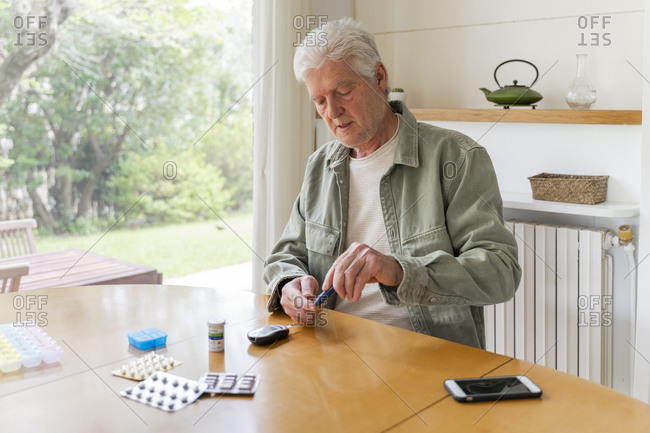 Retired diabetic senior man using glaucometer during blood sugar test while sitting at table