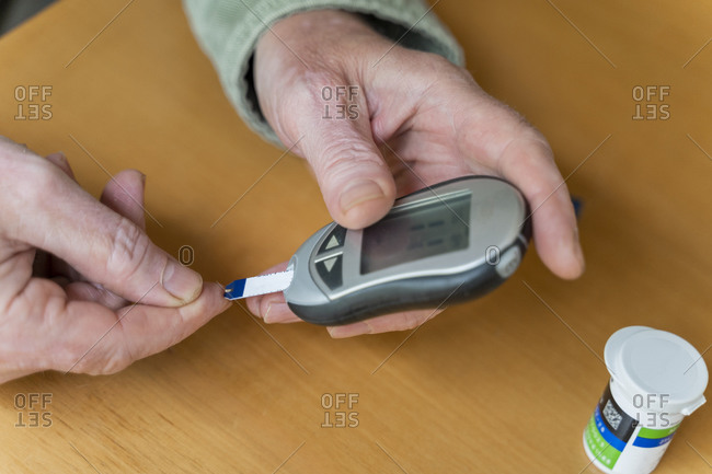 Cropped hands of glaucometer while examining blood sugar test at home
