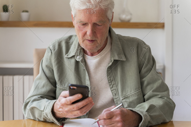 Retired diabetic senior man using smart phone while sitting with diary at home