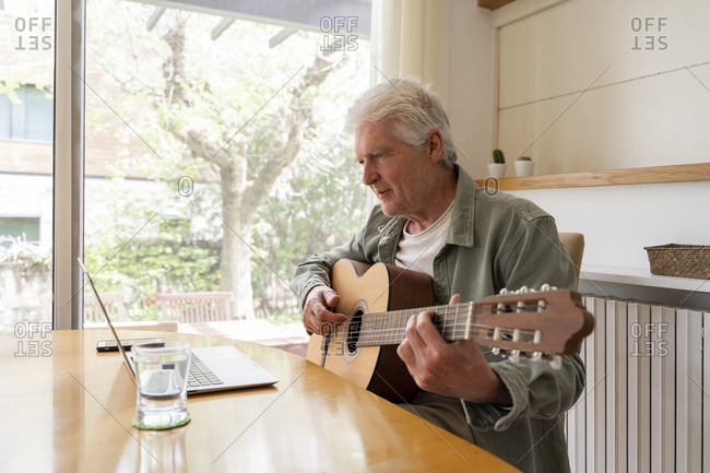 Retired elderly man learning to play guitar through online tutorials on laptop at home