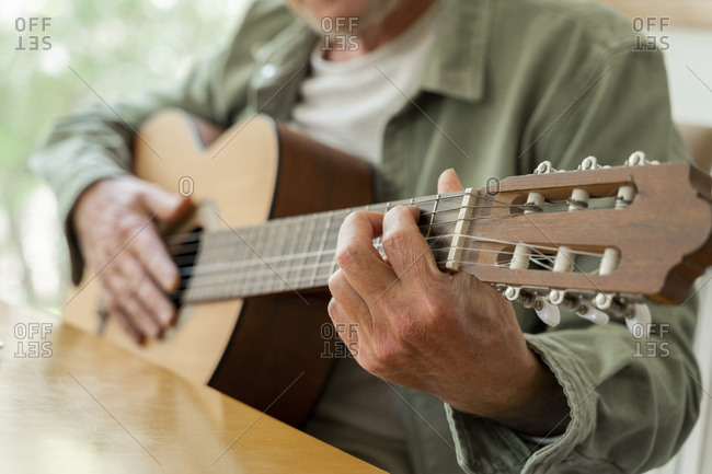 Midsection of retired man practicing guitar while sitting at home