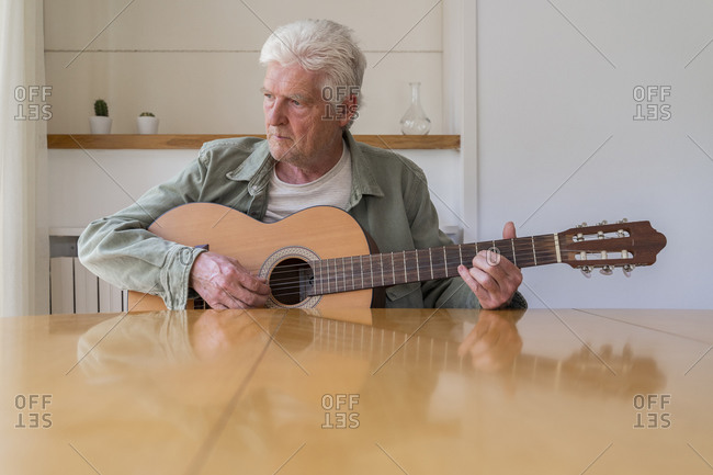 Thoughtful retired man practicing guitar while looking away at home
