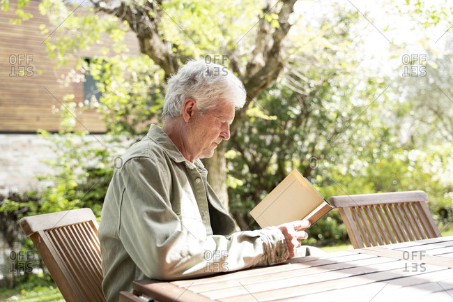 Side view of retired man reading novel while sitting at wooden table in back yard on sunny day