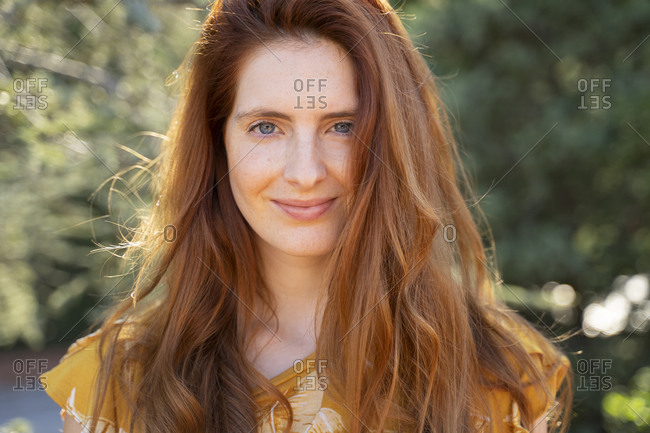Portrait of smiling redheaded woman outdoors