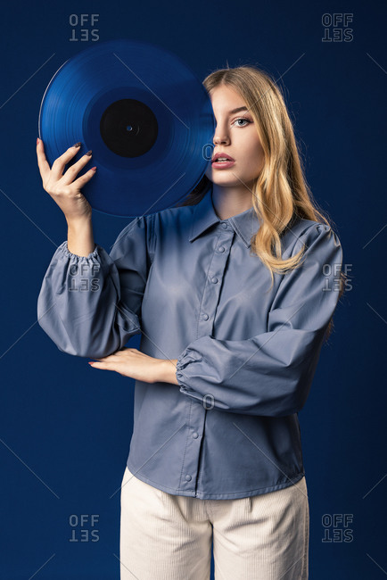 Blond woman with blue record in front of blue background