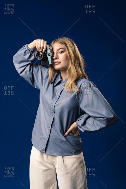 Blond woman using analog camera and looking at camera