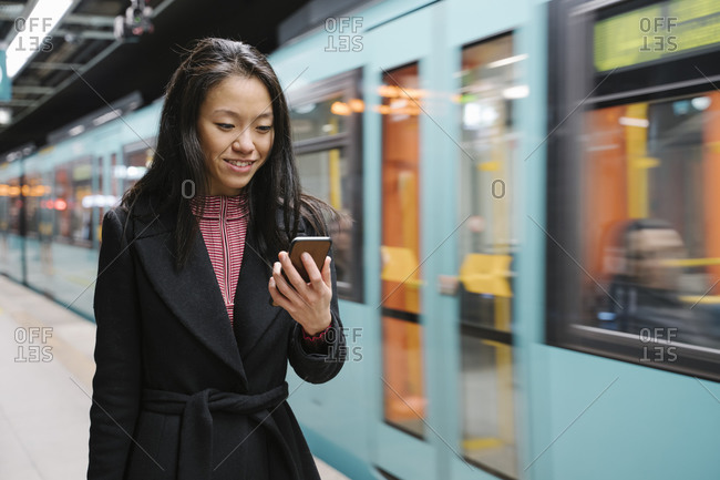 Young woman using smartphone in metro station