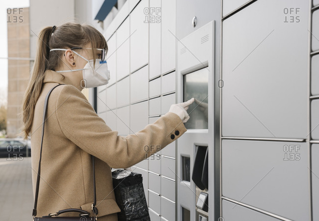 Woman wearing face mask and gloves using parcel terminal