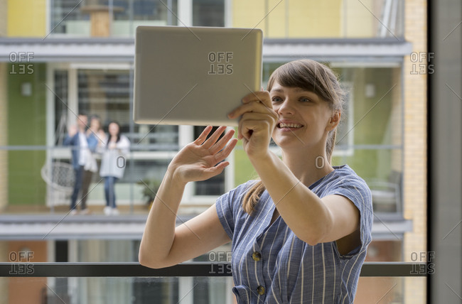 Portrait of smiling young woman using digital tablet for video chat with her neighbors