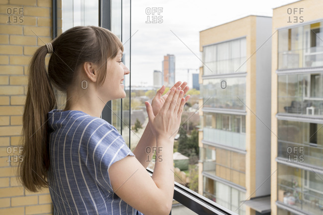 Smiling woman on balcony clapping hands