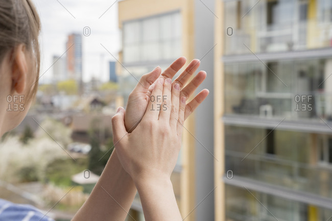 Crop view of woman clapping hands on balcony