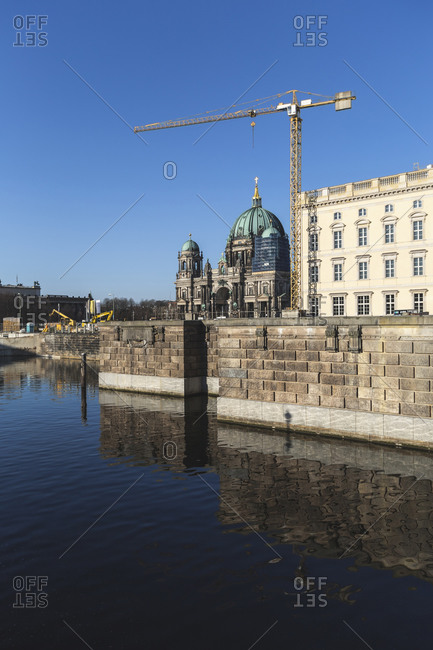 Germany- Berlin- Spree river canal with industrial crane and Berlin Cathedral in background