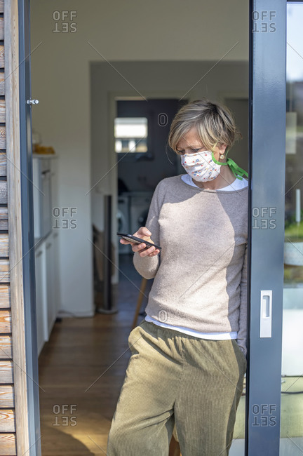 Mature woman with protective face mask using smart phone while standing at doorway