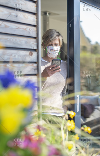 Woman with protective face mask using smart phone while standing at doorway during COVID-19 pandemic