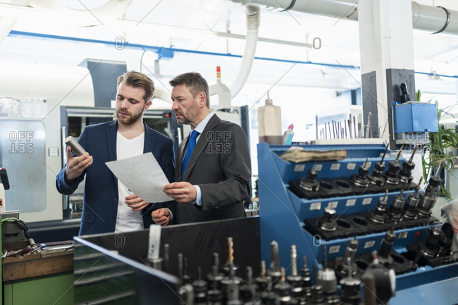 Two businessmen having a work meeting in a factory