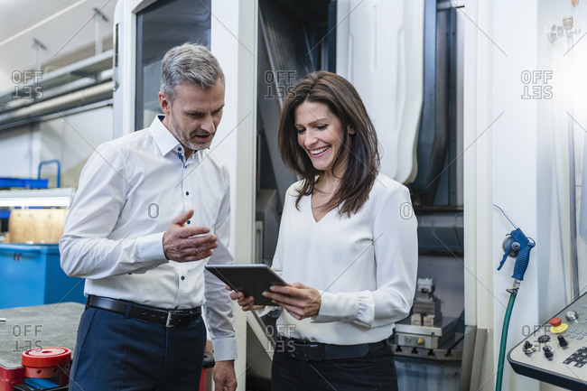 Businessman and businesswoman with tablet having a work meeting in a factory