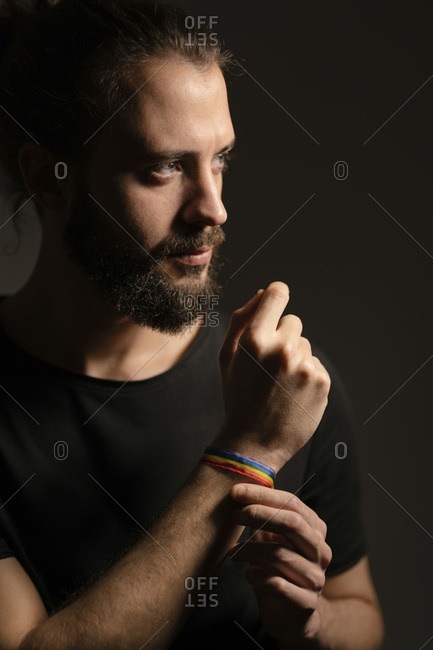 Portrait of bearded young man wearing rainbow wristband against dark background