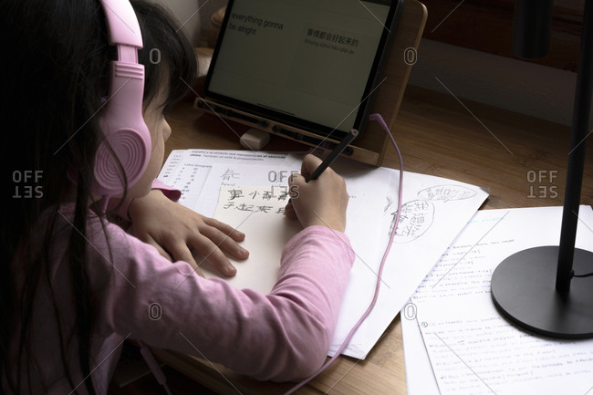 Girl wearing headphones learning Chinese language while using digital tablet at desk