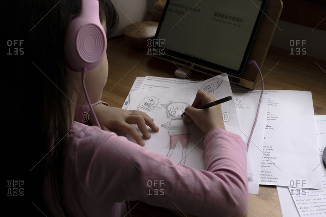 Girl wearing headphones drawing manga comics while using digital tablet at desk in house