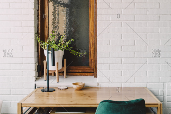 Wooden table and chair against houseplant on windowsill at home office