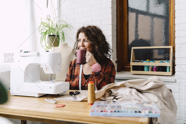 Woman sewing at home having a coffee break